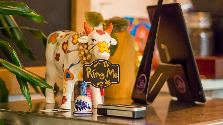 """Cow ornament with """"Ring me"""" sign around its neck on the counter at vegan restaurant Batin"""